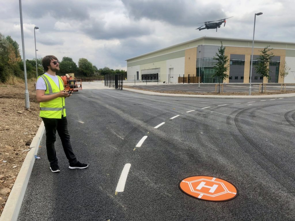 Rowan Johnson flying a drone at a new business development for Readie Construction