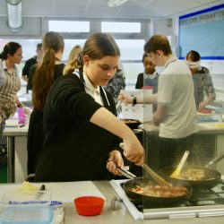 A student cooks in a Food Tech lesson at Admiral Lord Nelson School