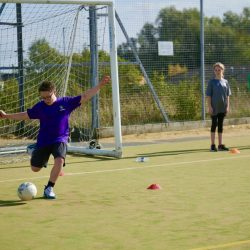 A student about to kick a ball in PE at Admiral Lord Nelson School